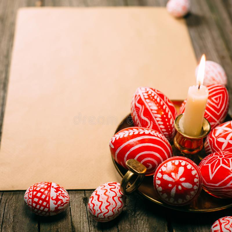Подсвечник крупного плана латунный с яичками пасхи красными с фольклорной белой стойкой картины на бумаге на деревенской таблице  стоковое изображение