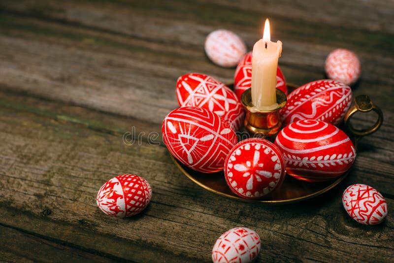 Подсвечник крупного плана латунный с яичками пасхи красными с фольклорной белой стойкой картины на деревенской таблице и яичками  стоковые фотографии rf