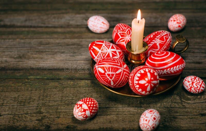 Подсвечник крупного плана латунный с яичками пасхи красными с фольклорной белой стойкой картины на деревенской таблице Украинские стоковая фотография