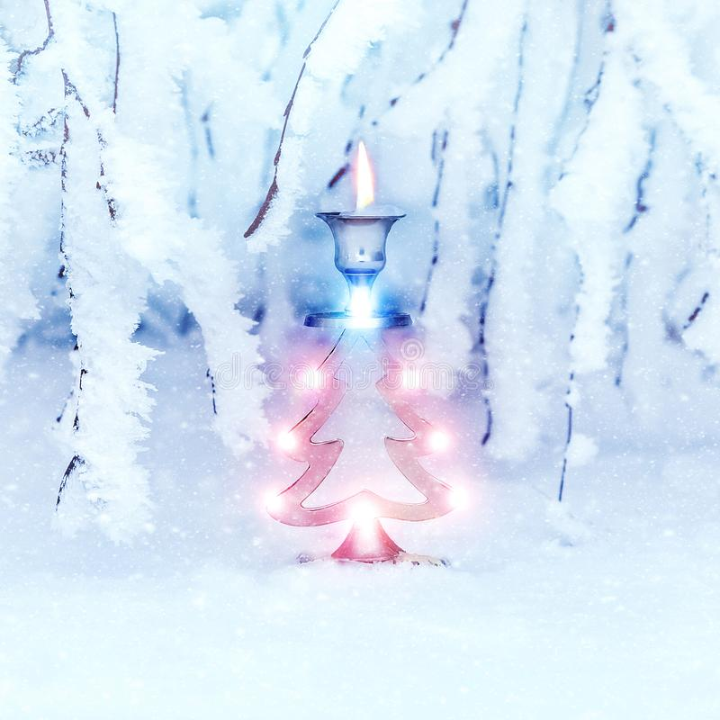 Подсвечник металла в форме дерева ` s Нового Года и свеча на фоне покрытых снег ветвей дерева стоковая фотография