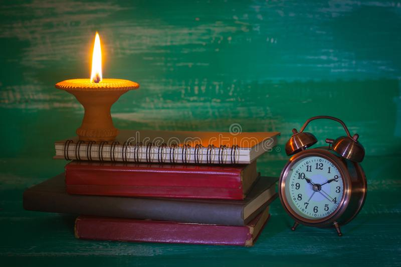 Подсвечник натюрморта на старой книге с будильником дальше стоковое изображение rf