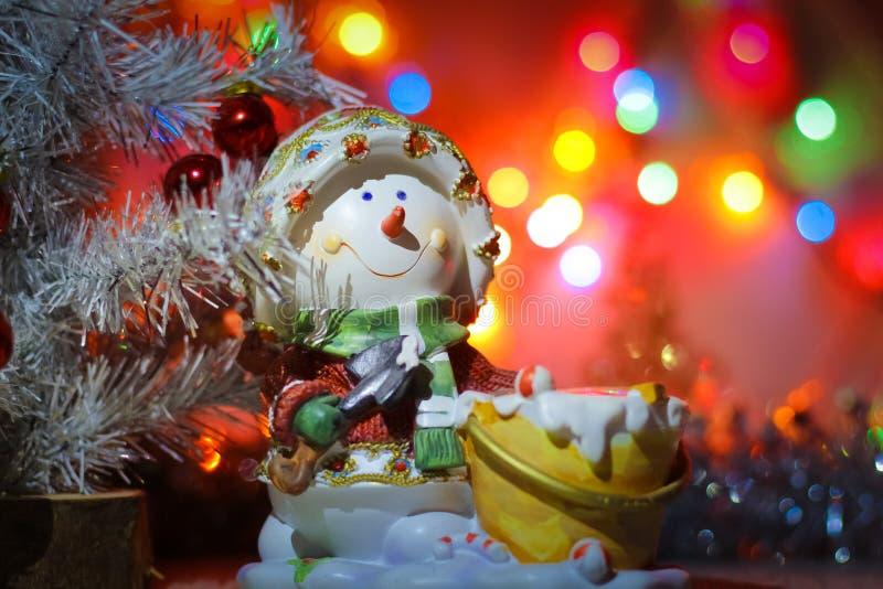 Подсвечник снеговика на предпосылке ярких покрашенных светов гирлянды и сусали стоковая фотография rf