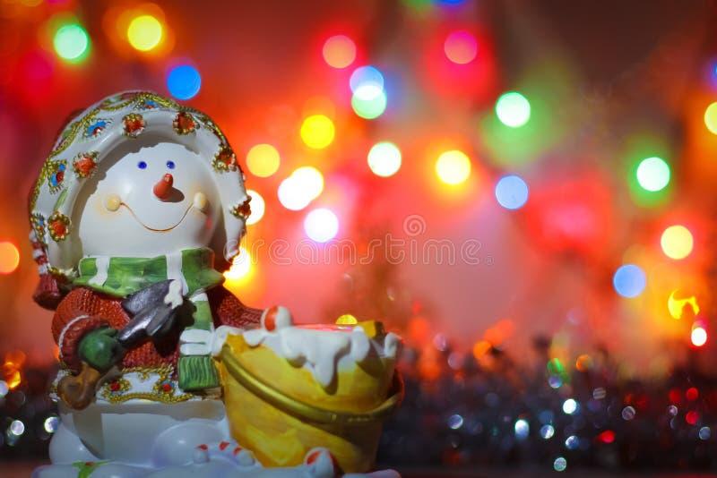 Подсвечник снеговика на предпосылке ярких покрашенных светов гирлянды и сусали стоковые изображения