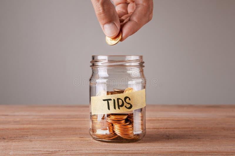 подсказки Стеклянный опарник с монетками и надписью наклоняет Человек держит монетку в его руке стоковое изображение