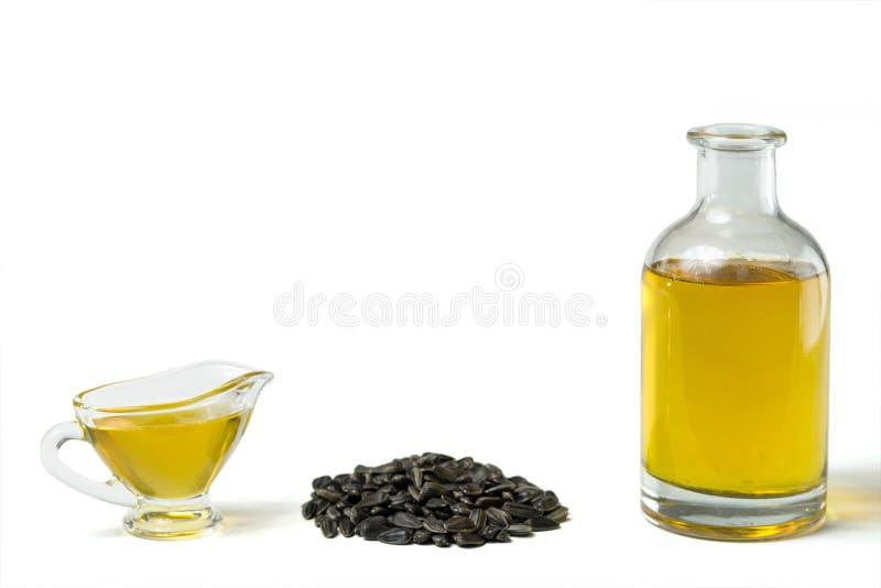 Подсолнечное масло в стеклянной шлюпке подливки, в бутылке, и пригорошня семян подсолнуха изолированных на белой предпосылке стоковое изображение
