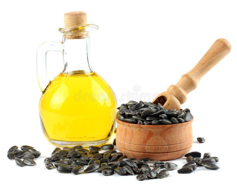 Подсолнечное масло в стеклянном кувшине и семенах изолированных на белой предпосылке стоковое фото rf