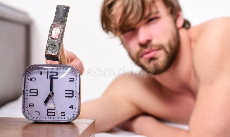 Подушка положения стороны человека бородатая надоеданная сонная около будильника Гай стучая со звенеть будильника молотка ширины стоковые изображения rf
