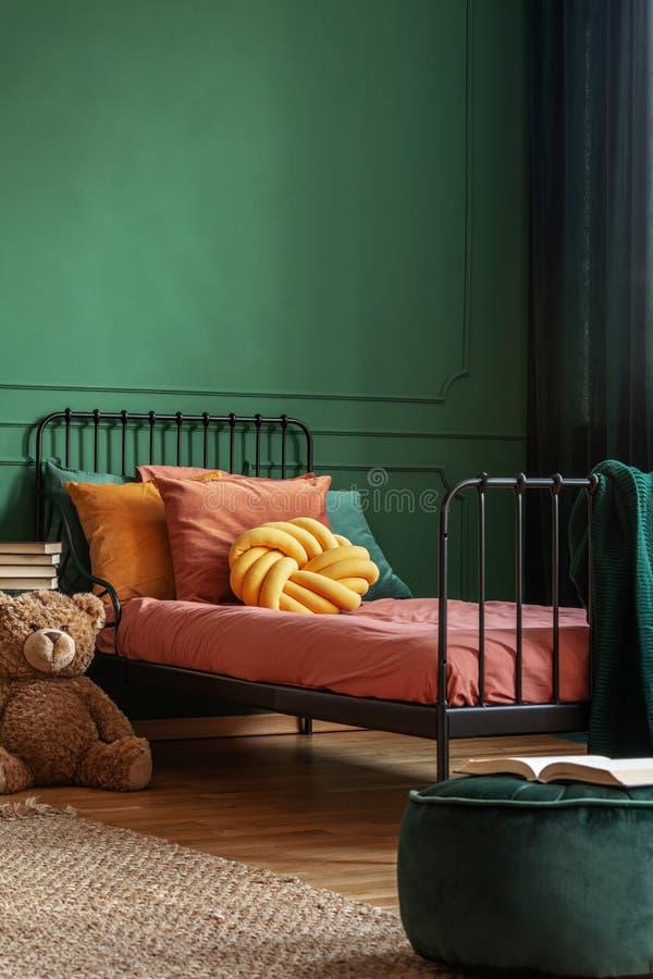 Подушка узла желтая на одиночной кровати металла с темным - оранжевые постельные принадлежности, космос экземпляра на пустой темн стоковое фото rf