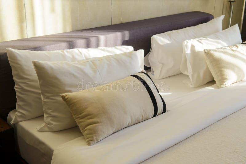 Подушки и простыни в роскошной комнате с солнечным светом в утре стоковые изображения