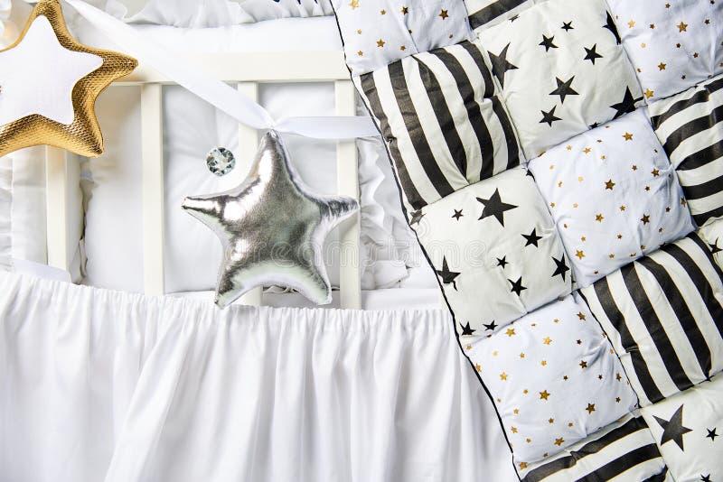 Подушки серебра и золота и одеяло заплатки сформированные звездой на белом конце кроватки младенца вверх стоковое фото