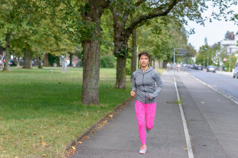Подходящая взрослая женщина бежать на тротуаре стоковое фото rf