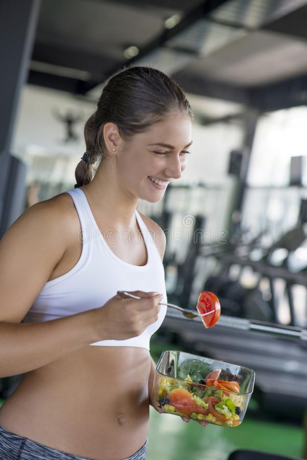 Подходящая женщина есть здоровый салат после разминки стоковые фотографии rf