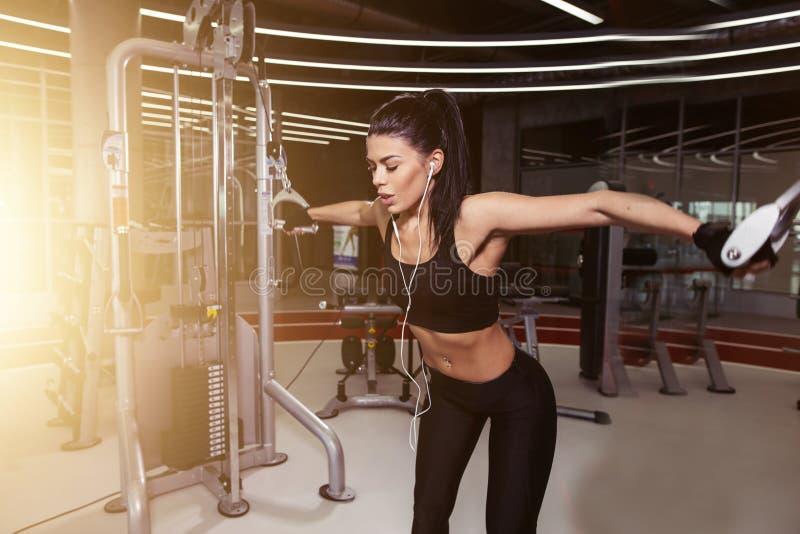 Подходящая женщина исполняет тренировку с кроссовером кабеля тренировк-машины в спортзале стоковое фото