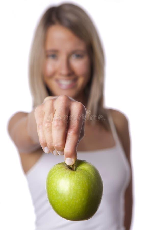 Подходящая женщина показывает яблоко стоковые изображения