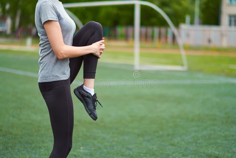 Подходящая женщина протягивая ее ногу для того чтобы нагревать На футбольном поле стоковая фотография rf