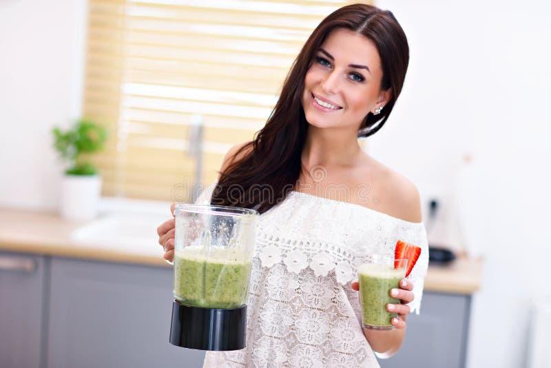 Подходящая усмехаясь молодая женщина подготавливая здоровый smoothie в современной кухне стоковые фотографии rf
