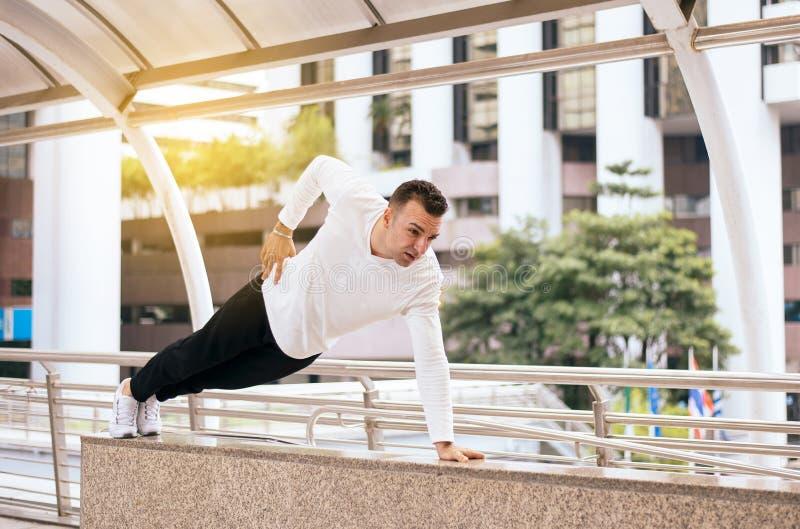 Подходящий делать человека нажимает вверх сильного мужчины с мышечным телом в городе стоковое фото rf