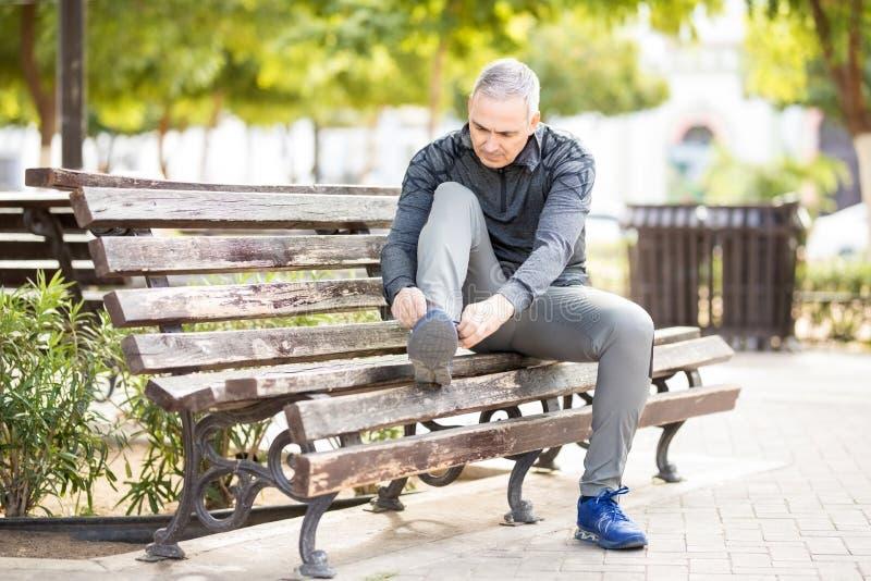 Подходящий и здоровый человек получая готовый пойти jogging в парке стоковая фотография