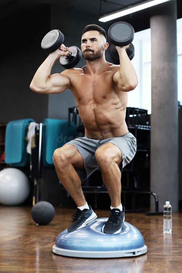 Подходящий и мышечный человек разрабатывая с bumbbells на гимнастическом шарике bosu полусферы в спортзале стоковое фото rf