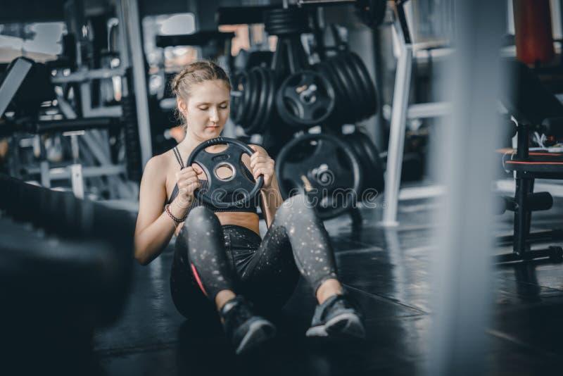 Подходящий красивый кавказец молодой женщины делая тренировку на крытой разминке в спортзале стоковые фотографии rf