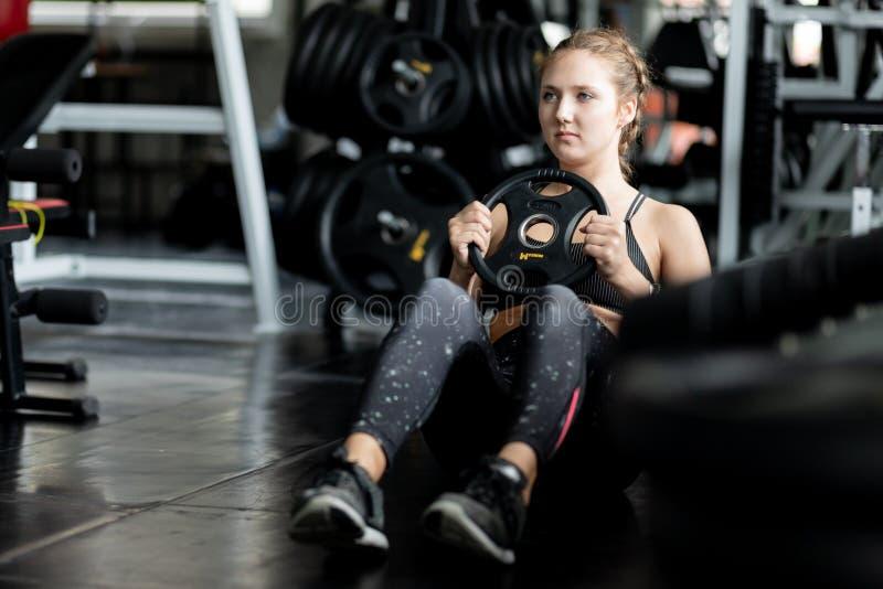 Подходящий красивый кавказец молодой женщины делая тренировку на крытой разминке в спортзале стоковая фотография