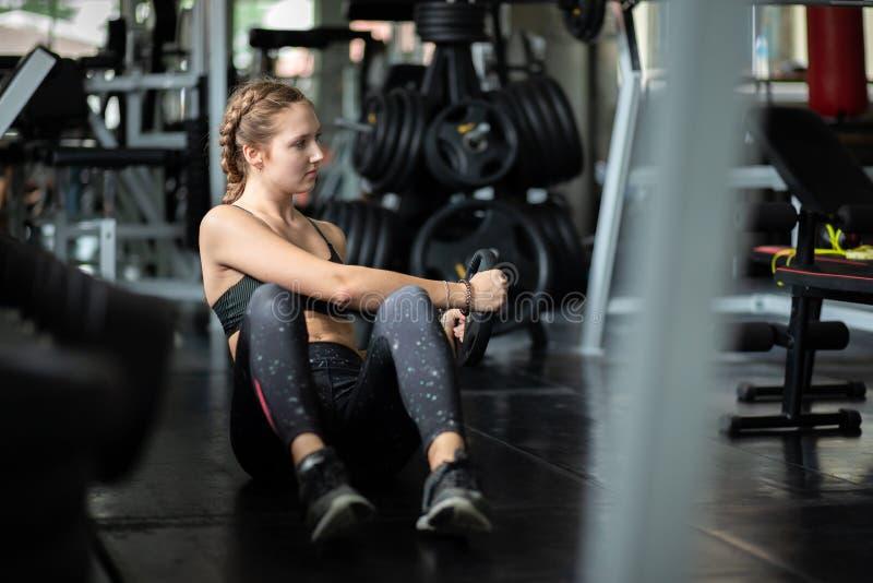 Подходящий красивый кавказец молодой женщины делая тренировку на крытой разминке в спортзале стоковые изображения