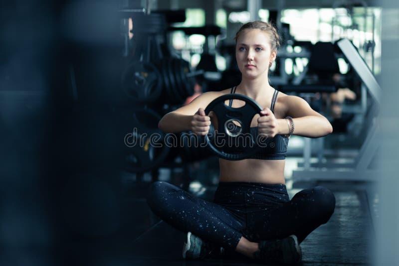 Подходящий красивый кавказец молодой женщины делая тренировку на крытой разминке в спортзале стоковые изображения rf