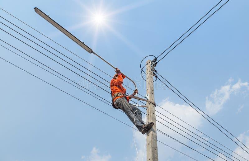 Подъем электрика работая в высоте на поляке с ремнем безопасности стоковые фото