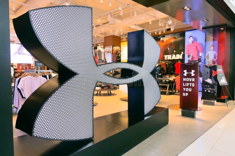ПОД компанией sportswear ПАНЦЫРЯ американской основанной в 1996 изготовляет спорт обуви и вскользь одежды раскрывают новый большо стоковая фотография