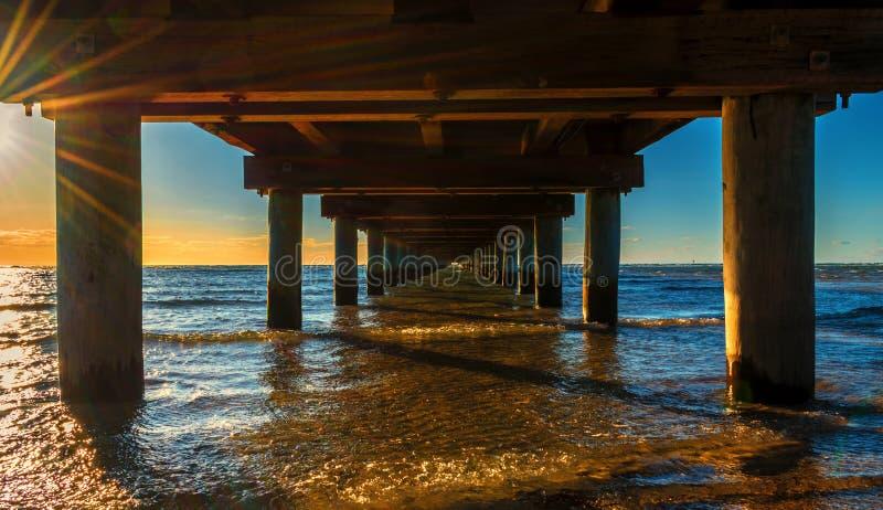Под пристанью на красивом золотом оранжевом заходе солнца стоковая фотография