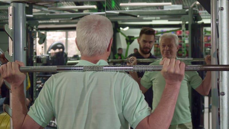 Поезда старшего человека на спортзале стоковая фотография
