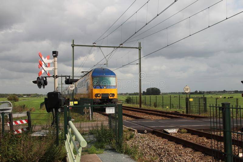 Поезд двойной палуба на железнодорожном переезде в Moordrecht стоковое изображение