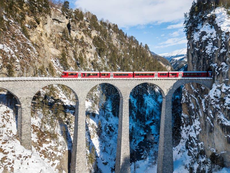 Поезд красного пассажира швейцарский проходя на известный виадук Landwasser стоковое фото rf