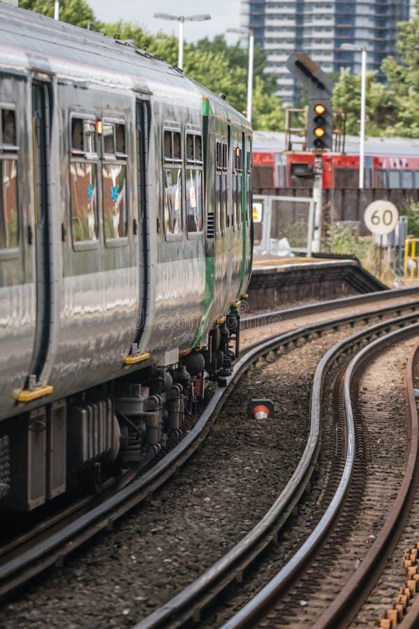 Поезд Лондона покидая платформа стоковое фото