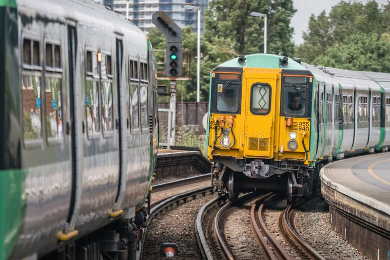 Поезд Лондона приезжая на платформу стоковая фотография
