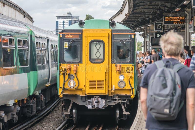 Поезд Лондона приезжая на платформу стоковое фото