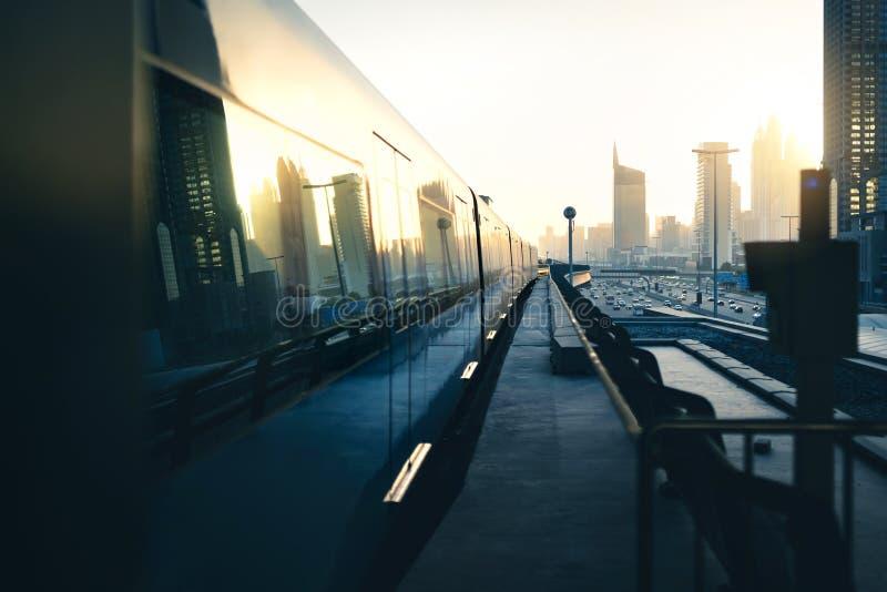 Поезд метро и метро в городе Футуристический современный общественный транспорт Железнодорожная сеть Дубай на заходе солнца со зд стоковая фотография