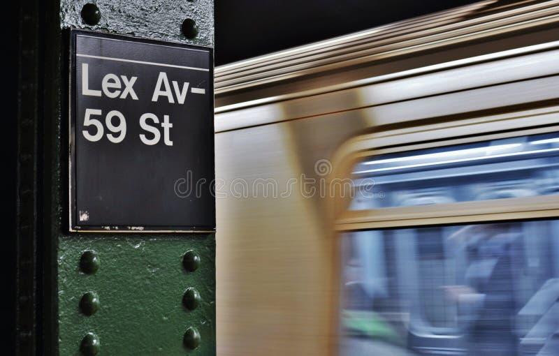 Поезд перехода города Манхэттена бульвара Lexington знака метро NYC расположенный на окраине города приезжая стоковое изображение