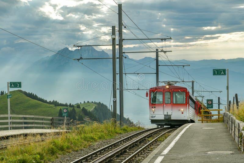 Поезд приближается к железнодорожному вокзалу на вершине горы Риги в кантоне Швиц, Швейцария стоковое фото