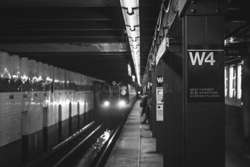 Поезд причаливая платформе на станции метро улицы запада 4-ой в Манхэттене, Нью-Йорке стоковое изображение