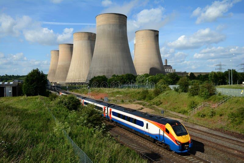 Поезд проходя электростанцию стоковые изображения