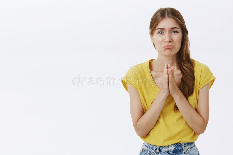 Пожалуйста мне нужна ваша помощь Портрет придурковатой милой пища девушки в желтой футболке держа руки внутри молит морща губы ес стоковое фото rf