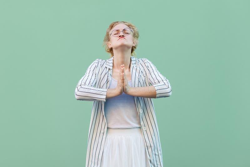 Пожалуйста помогите или простите мне Портрет надеющийся молодой белокурой женщины в белой striped блузке с eyeglasses стоя с рука стоковое фото rf