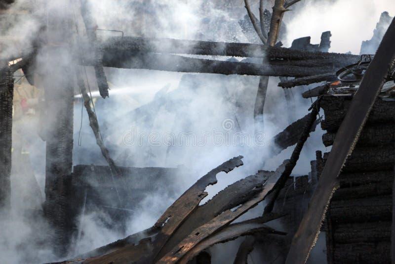 пожарище руины и остатки, который сгорели деревянного дома Сгорели сгоренный швырок в густом дыме стоковое фото rf