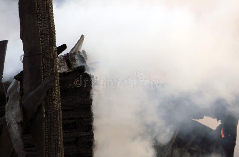 пожарище руины и остатки, который сгорели деревянного дома Сгорели сгоренный швырок в густом дыме стоковые изображения