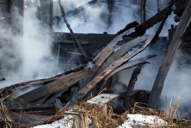 пожарище руины и остатки, который сгорели деревянного дома Сгорели сгоренный швырок в густом дыме стоковое изображение