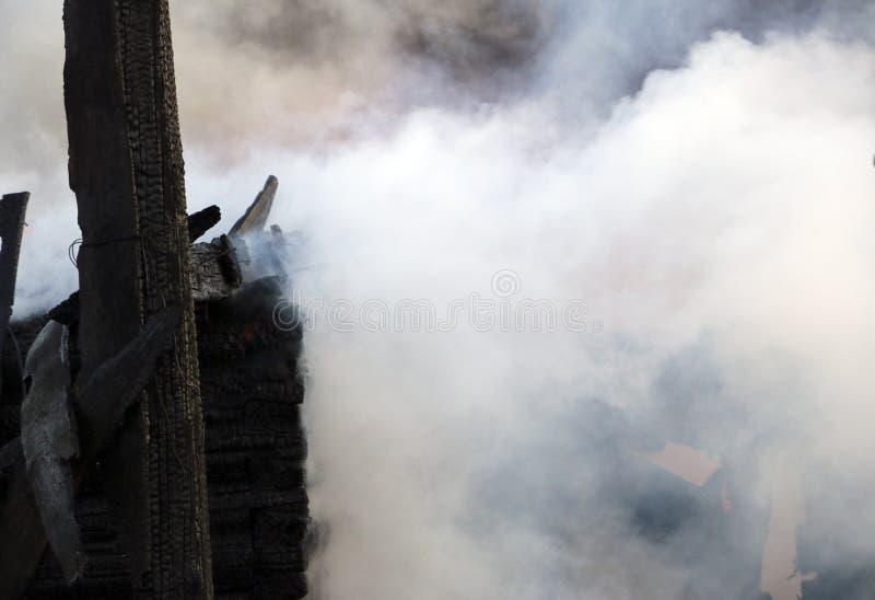 пожарище руины и остатки, который сгорели деревянного дома Сгорели сгоренный швырок в густом дыме стоковые фото