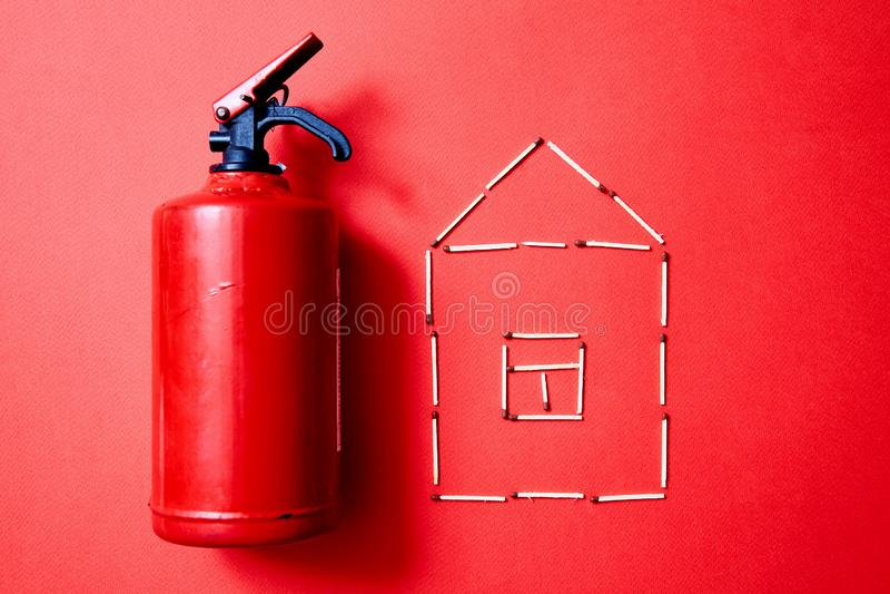 Пожарная безопасность, или концепция безопасностью и защитой Огнетушитель и диаграмма дома спичек стоковые изображения rf
