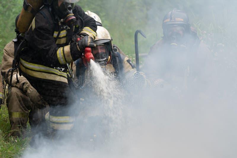 Пожарная команда федеральной пожарной службы во время огня - тушащ, тренируя для того чтобы преодолевать зону огня психологическо стоковые фотографии rf