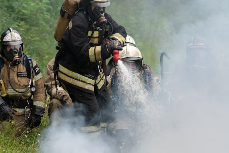 Пожарная команда федеральной пожарной службы во время огня - тушащ, тренируя для того чтобы преодолевать зону огня психологическо стоковые изображения